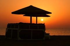 Deckchair on a beach. Empty deckchairs with umbrella on the beach at sunrise Stock Image