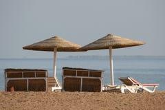 Deckchair on a beach. Empty deckchairs with umbrella on the beach Stock Photos