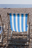 Deckchair. A blue and white striped deckchair on a pebble beach looking out to sea Royalty Free Stock Photo