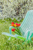 Deckchair and a bouquet of tulips in the garden Royalty Free Stock Image