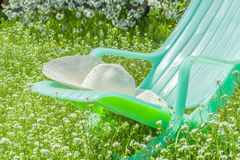 Deckchair and hat on sunny spring lawn. Green chaise and a white hat on a sunny spring meadow in a lush garden close-up, backlit Stock Image