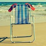 Deckchair i pomarańczowe klapy na plaży z retro skutkiem, zdjęcia stock