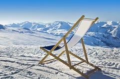 Deckchair im Schnee, der die Alpen gegenüberstellt Stockbilder