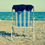 Deckchair and man swimsuit on the beach, with a retro effect. A deckchair and a man swimsuit on the beach, with a retro effect Stock Photo