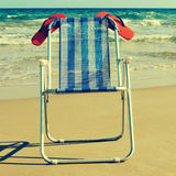 Deckchair and orange flip-flops on the beach, with a retro effec. A deckchair with a pair of orange flip-flops on the beach, with a retro effect Stock Photos