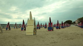 Deckchair and parasols arranged on the sandy beach. Sun shades and deckchairs arranged in lines on the sandy beach stock video footage