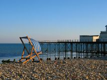 Deckchair by the Pier. A deckchair on the beach at Bognor Regis Sussex England royalty free stock images
