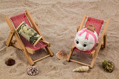 Deckchair with piggy bank and dollars Royalty Free Stock Photos