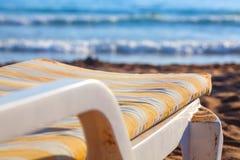 Deckchair on sandy beach of blue sea. Sun bed on sandy beach of blue sea Stock Photos