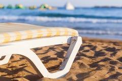 Deckchair on sandy beach of blue sea. Sun bed on sandy beach of blue sea Royalty Free Stock Images
