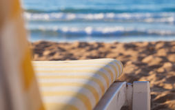 Deckchair on sandy beach of blue sea. Sun bed on sandy beach of blue sea Royalty Free Stock Photos