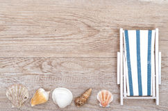 Deckchair and sea shells on wood Stock Image