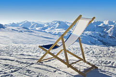 Deckchair in the snow facing the Alps Stock Images
