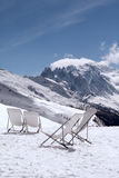 Deckchair in snow in a snow-covered mountain landscape Stock Photo