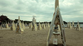 Deckchair and sun shades arranged on the beach. Sun shades and deckchairs arranged in lines on the sandy beach stock video footage