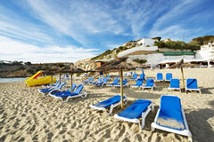 Deckchair and sunshade on a beach of ibiza. Many deckchairs on a beach of ibiza island during summer Royalty Free Stock Images