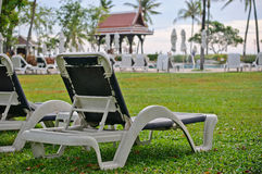 Deckchair in a swimming pool. Deckchair on grass in swimming pool at resort in Thailand Royalty Free Stock Image
