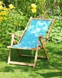 Deckchair in tuin Stock Afbeelding