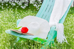 Deckchair, tulip. scarf and hat in the garden Stock Photography