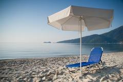 Deckchair under umbrella. Deckchair under white umbrella. Blue sky and water Royalty Free Stock Photo