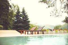 Deckchairs в бассейне курортного отеля Стоковое Фото