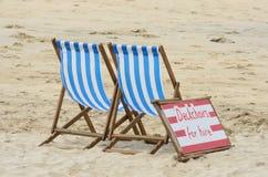 Deckchairs на найме на пляже Стоковое Изображение
