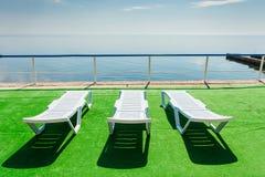 3 deckchairs на пляже, смотря на вне к морю Стоковые Изображения