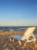 Deckchairs на пляже с яркими солнцем и волнами Стоковое Фото