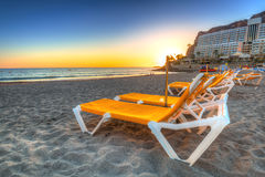 Deckchairs на пляже Taurito на заходе солнца Стоковое Фото