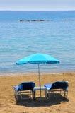 在遮阳伞之下的蓝色deckchairs在海边 库存照片