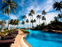 在热带度假旅馆水池的Deckchairs 免版税库存照片