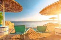 伞和两空的deckchairs在岸沙子靠岸 免版税图库摄影