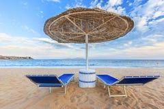 伞和两空的deckchairs在岸沙子靠岸 库存照片