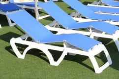Deckchairs al lato della piscina Immagini Stock Libere da Diritti