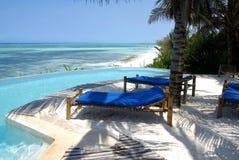Deckchairs around resort swimming-pool Stock Photos