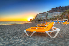 Deckchairs auf dem Strand von Taurito bei Sonnenuntergang Stockbild