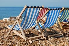 Deckchairs auf einem Pebble Beach Stockbilder