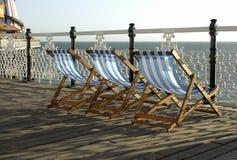 Deckchairs auf Pier lizenzfreie stockbilder