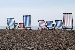 Deckchairs auf Schindelstrand. Großbritannien Stockfoto