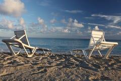 Deckchairs on the beach. Deckchairs on the background blue sea Stock Photos