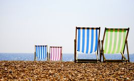 Deckchairs on the beach. Four deckchairs on a summers evening, Brighton beach royalty free stock photo