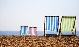 Deckchairs on the beach. Four deckchairs on a summers evening, Brighton beach Royalty Free Stock Photo
