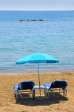 Deckchairs blu sotto il parasole sulla spiaggia Fotografie Stock
