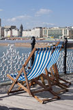 Deckchairs. Blue and white striped deckchairs on Brighton Pier facing the beach Stock Photography