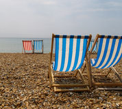 Deckchairs on Brighton Beach. Deckchairs on Brighton beach awaiting sunbathers, blue stripes with one odd red striped Royalty Free Stock Photography