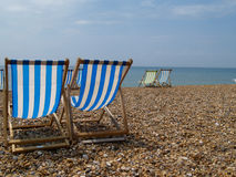 Deckchairs close up on left of frame. Stock Photography