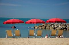 Deckchairs con las sombrillas en la playa Foto de archivo