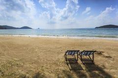 Deckchairs de los pares en la playa en la puesta del sol Fotografía de archivo libre de regalías