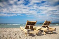 Deckchairs de madera en la playa vacía Fotografía de archivo libre de regalías
