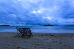 Deckchairs dos pares na praia como o tom azul Foto de Stock Royalty Free